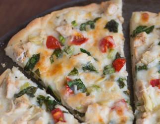 Pizza au poulet et légumes avec une sauce blanche à l'ail